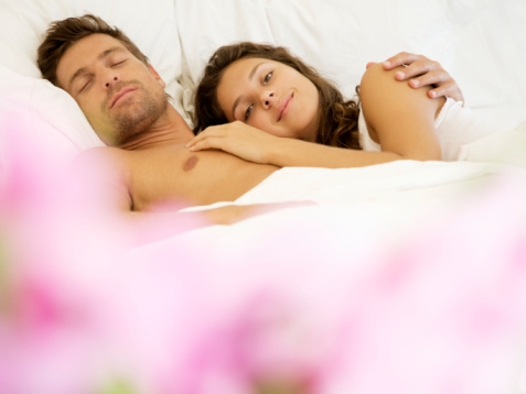 Young woman resting head on man's chest in bed
